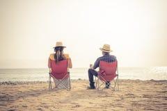 Pares lindos que disfrutan de puesta del sol en la playa fotos de archivo