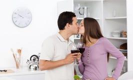 Pares lindos que se besan con los vidrios de vino rojo Fotografía de archivo libre de regalías