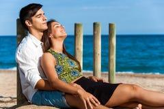 Pares lindos que se relajan en la playa Imagen de archivo libre de regalías