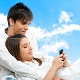 Pares lindos que socializan con el teléfono elegante al aire libre. Fotografía de archivo libre de regalías