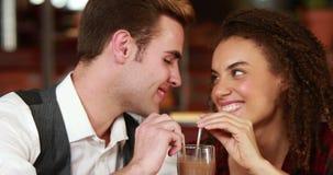 Pares lindos que sorben una bebida fresca junto metrajes
