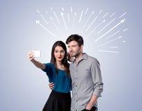 Pares lindos que toman el selfie con las flechas Imagen de archivo