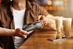 Pares lindos una fecha en el café que paga por la tarjeta de crédito Imagen de archivo libre de regalías