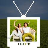 Pares locos que se sientan en el sofá en el campo verde   Foto de archivo libre de regalías