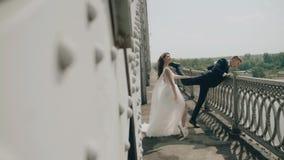 Pares loucos novos alegres do casamento que têm o divertimento na borda da ponte Jovens alegres Bom modo video estoque