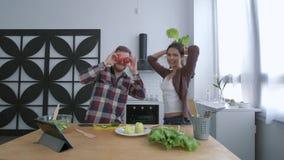 Pares loucos que enganam ao redor e que riem com tomates e ervas ao cozinhar a salada vegetal na refeição matinal para o bem-esta video estoque