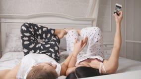 Pares loving alegres felizes que fazem o selfie na cama, no indivíduo atrativo novo e na menina encontrando-se nos pijamas foto de stock royalty free