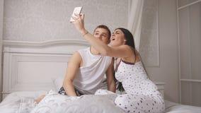 Pares loving alegres felizes que fazem o selfie na cama, no indivíduo atrativo novo e na menina sentando-se nos pijamas fotos de stock