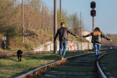 Pares loving com um cão na trilha railway A vista da parte traseira Foto de Stock