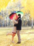 Pares loving felizes que abraçam com guarda-chuva colorido junto no dia ensolarado morno sobre as folhas de voo amarelas fotos de stock royalty free