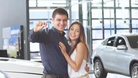 Pares loving felizes que abraçam perto de seu carro luxuoso novo no negócio vídeos de arquivo