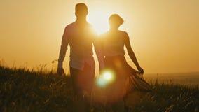 Pares loving - homem novo corajoso e menina bonita na silhueta do por do sol filme