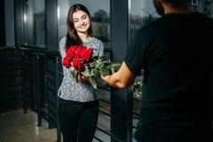 Pares loving, homem que dá um ramalhete das rosas a sua mulher Valen imagem de stock