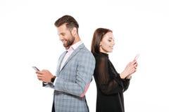 Pares loving novos alegres que conversam por telefones Fotografia de Stock Royalty Free
