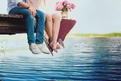 Pares loving novos consideravelmente fortes que sentam-se na ponte sobre o rio, ao lado de um ramalhete das peônias, estilo de vi Imagens de Stock