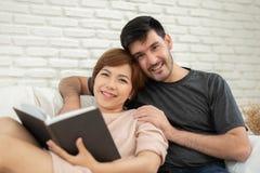 Pares loving novos felizes que leem um livro imagem de stock