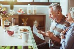 Pares loving positivos que apreciam seu café da manhã na cozinha Foto de Stock
