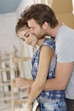 Pares loving que abraçam em casa a renovação fotos de stock