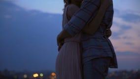 Pares loving que abraçam-se e que sussurram a ternura no telhado no crepúsculo vídeos de arquivo