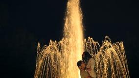 Pares loving que beijam perto da fonte filme
