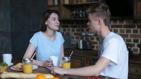 Pares loving que comem o café da manhã na cozinha moderna filme
