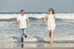 Pares loving que correm na praia no tempo do dia Foto de Stock