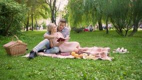 Pares loving que discutem o livro que senta-se confortavelmente no tapete durante o piquenique, data romântica vídeos de arquivo