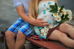 Pares loving que esperam o bebê que guarda as mãos fotos de stock royalty free
