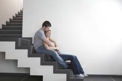 Pares loving que sentam-se em etapas na casa Fotografia de Stock Royalty Free