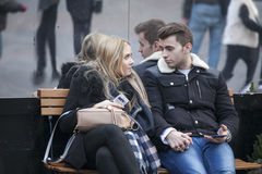 Pares loving que sentam-se em um banco no jardim de Covent na frente de uma parede espelhada imagem de stock royalty free