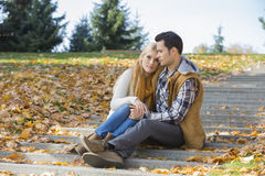 Pares loving que sentam-se junto em etapas no parque durante o outono fotos de stock