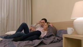Pares loving que sentam-se na cama, usando o smartphone, discutindo fotos novas Fotografia de Stock Royalty Free