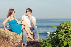 Pares loving que sentam-se na praia no tempo do dia Fotografia de Stock Royalty Free
