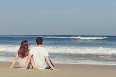 Pares loving que sentam-se na praia no tempo do dia Fotos de Stock
