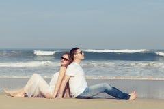 Pares loving que sentam-se na praia no tempo do dia Imagens de Stock Royalty Free