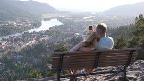 Pares loving românticos que sentam-se no banco de madeira e que admiram a cidade e o rio no vale filme