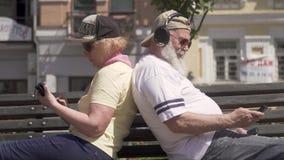 Pares maduros à moda que relaxam no banco na cidade filme