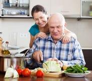 Pares maduros alegres que cocinan la comida Imagen de archivo