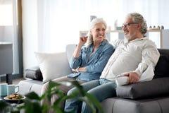 Pares maduros alegres que ven la TV en el apartamento imagen de archivo libre de regalías