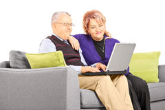 Pares maduros asentados en el sofá que mira el ordenador portátil Fotos de archivo