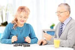 Pares maduros assentados na tabela que joga dominós em casa Fotos de Stock Royalty Free