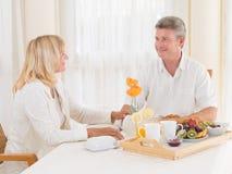 Pares maduros cariñosos que gozan de un desayuno sano que sonríe en uno a Imagenes de archivo