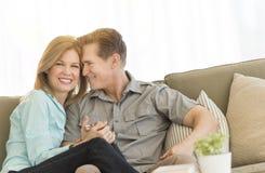 Pares maduros cariñosos que se sientan en Sofa At Home Foto de archivo