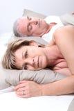 Pares maduros colocados na cama fotografia de stock royalty free