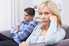 Pares maduros com as dificuldades do relacionamento que sentam-se no sofá foto de stock