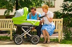 Pares maduros con el carro de bebé Fotos de archivo libres de regalías