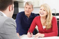 Pares maduros con el documento de firma del consejero financiero en casa Foto de archivo libre de regalías