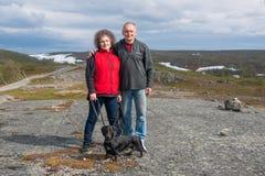 Pares maduros con el perro basset en montañas, Noruega Fotografía de archivo