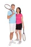 Pares maduros con las raquetas de tenis Fotografía de archivo libre de regalías