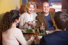 Pares maduros con los amigos que comen la cena y el vino en el restaurante foto de archivo